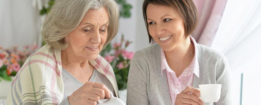 Ung kvinde besøger ældre kvinde og sludrer over en kop kaffe, som en del af besøgstjenesten i Røde Kor på Møn.
